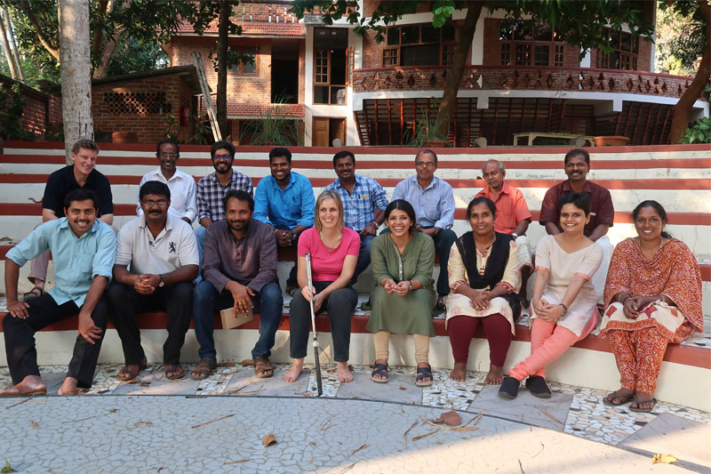 Group picture of kanthari staff sitting on amphitheatre posing for picture and all are smiling